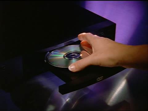 stockvideo's en b-roll-footage met high angle zoom in woman's hand putting dvd into dvd player + closing - dvd
