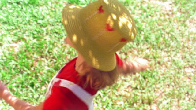 vidéos et rushes de high angle ms zoom in young girl wearing straw hat looking up + spinning outdoors / florida - children only
