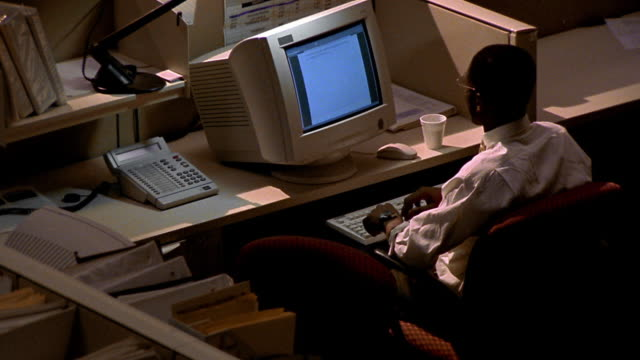 high angle zoom out Black man working late at computer with desk lamp in dark office with cubicles / he checks watch