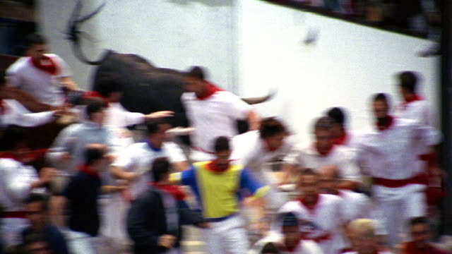 high angle PAN zoom out crowd of people running with bulls/ two bulls falling down / Running of the Bulls / Pamplona