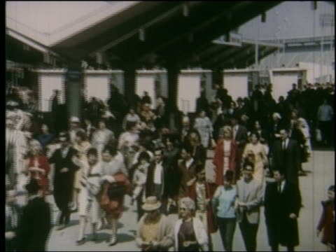 stockvideo's en b-roll-footage met 1964 high angle zoom out crowd walking thru entrance of ny world's fair - 1964
