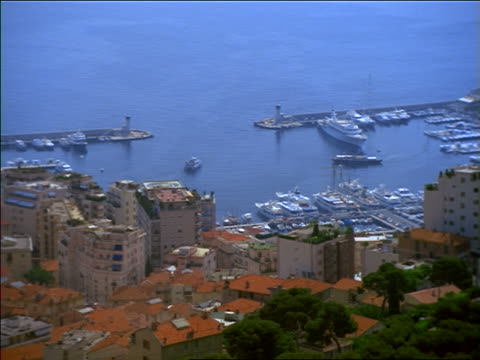 high angle zoom out from boats in harbor to wide shot of cityscape / monte carlo, monaco - monte carlo stock-videos und b-roll-filmmaterial
