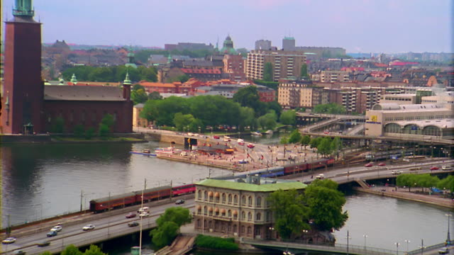 high angle zoom out from building and bridge over river to wide shot stockholm cathedral + surrounding city / sweden - 1993 stock videos & royalty-free footage