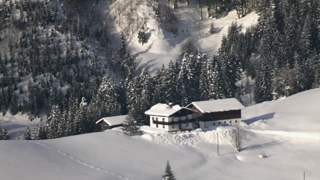 High angle zoom out from snow-covered chalets on Rinnberg Mountain / Austria