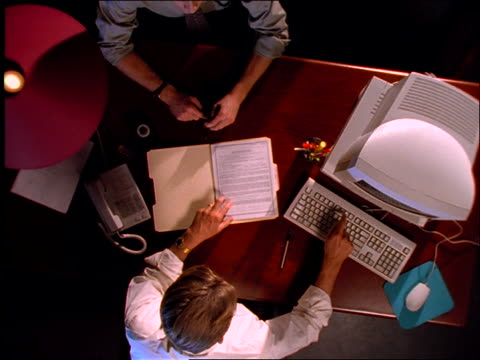 high angle zoom out of 2 businessmen going over contract on desk