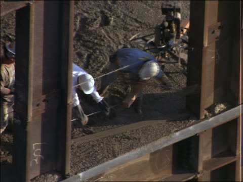 vidéos et rushes de high angle zoom out of building under construction / worker laying cement - cinématographie