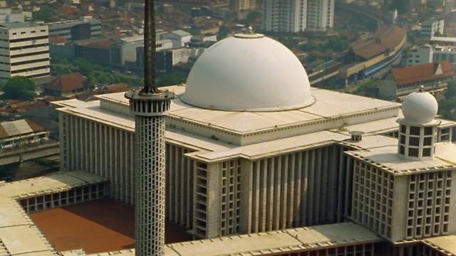 high angle zoom out to wide shot modern mosque building / smoggy cityscape in background / jakarta - jakarta stock videos & royalty-free footage