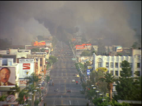 vídeos de stock e filmes b-roll de high angle zoom out to wide shot of smoke over los angeles street during riots - 1992
