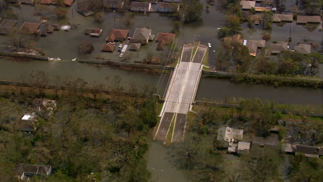 high angle zoom out wide shot chinook helicopter flying over bridge to levee breach / zoom in sandbags /new orleans louisiana - sandbag stock videos & royalty-free footage