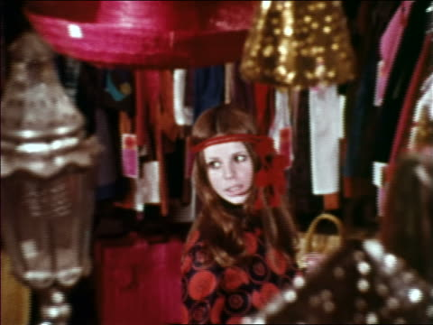 1969 high angle zoom out woman in headband turning to talk to someone in clothing store / NYC / industrial