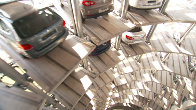 High Angle_crane pan-right push-in - Cars fill storage slots in a huge tower garage. / Wolfsburg, Germany