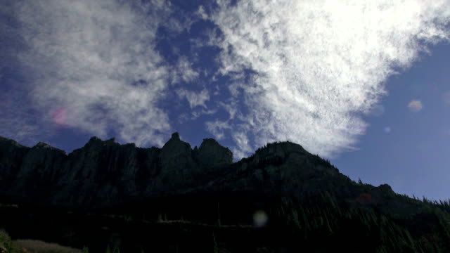 high cirrus clouds passing over jagged mountain ridge line. - glacier national park us stock videos and b-roll footage