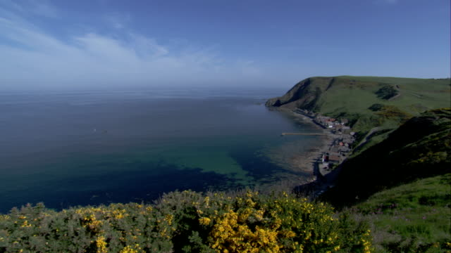 high cliffs surround the tiny village of crovie, coast of aberdeenshire, scotland. available in hd. - クロヴィー点の映像素材/bロール