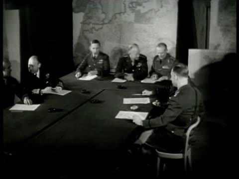 High Command at table w/ map BG General Dwight D Eisenhower talking w/ Field Marshall Bernard Montgomery at table RAF Air Marshall Arthur Tedder...