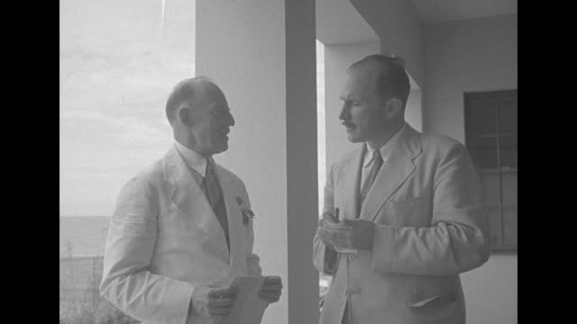 us high commissioner francis sayre sr standing on balcony ships on ocean in bg / ms sayre talking to reporter arthur menken who is writing notes and... - general macarthur stock videos and b-roll footage