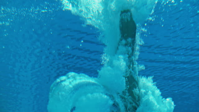slo mo ld high diver doing an underwater flip when hitting the pool - underwater diving stock videos & royalty-free footage