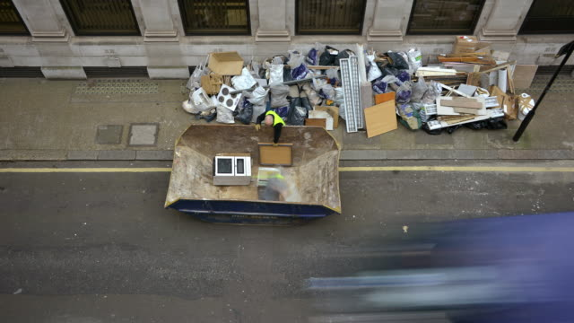 stockvideo's en b-roll-footage met a high downward view of a london street with rubbish and builders rubble from an office clearance being stacked on the pavement as a skip is delivered and filled with a rubble then lifted on to a lorry and taken away - afvalverwerking