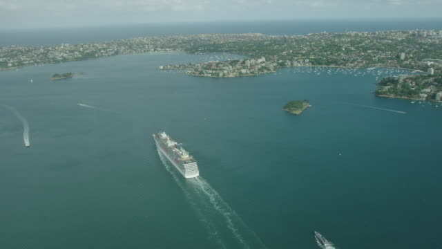 high drone aerial cruise ship in Sydney Harbour seeing over Clark Island Point Piper over Eastern Suburbs and out to Pacific Ocean following behind...