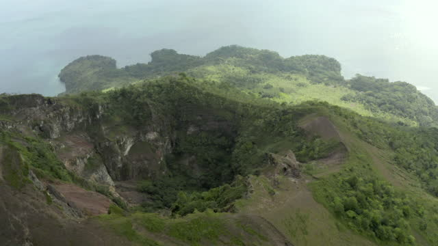 vídeos y material grabado en eventos de stock de a high elevation aerial over an overgrown volcanic crater with steep forested slopes leading to brightly lit ocean - banda, indonesia - brightly lit