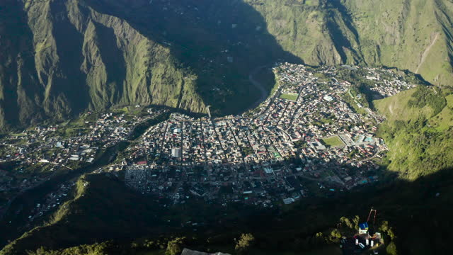high elevation aerial: sprawling city nests between tall lush foothills in evening sunshine - banos, ecuador - ecuador stock videos & royalty-free footage