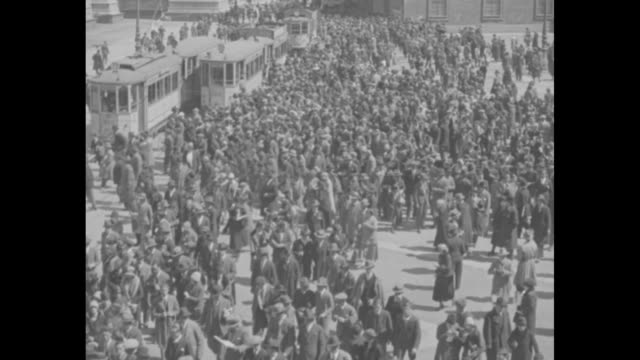high elevation shot of crowds and streetcars in street / pan crowds waving hats above heads and cheering king victor emmanuel in milan square; the... - 1920 video stock e b–roll