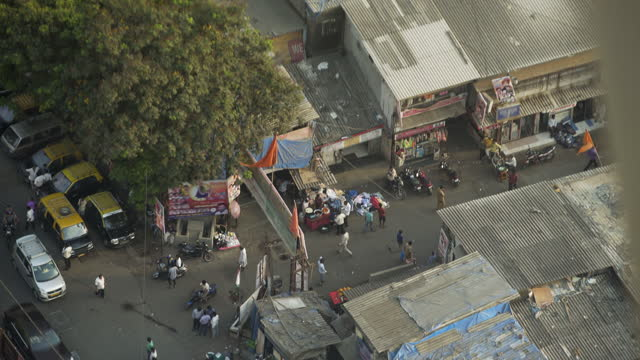 high elevation view of cars, motorcycles, and pedestrians wandering street around small shops - mumbai, india - election stock videos & royalty-free footage