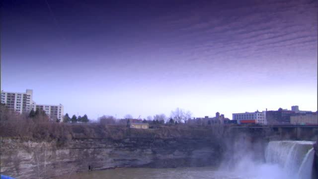 high falls waterfall & genesee river, trestle w/ freight train moving out of frame, trees w/ bare branches, cirrocumulus clouds in sky, mid-rise... - cirrocumulus stock videos & royalty-free footage