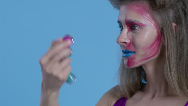 high fashion blond model in multi colored stage make-up holds a lot of multi colored nail polish bottles. fashion video. - supermodel stock videos and b-roll footage