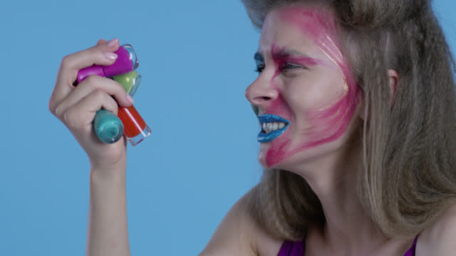 high fashion blond model in multi colored stage make-up holds a lot of multi colored nail polish bottles. fashion video. - lip liner stock videos & royalty-free footage