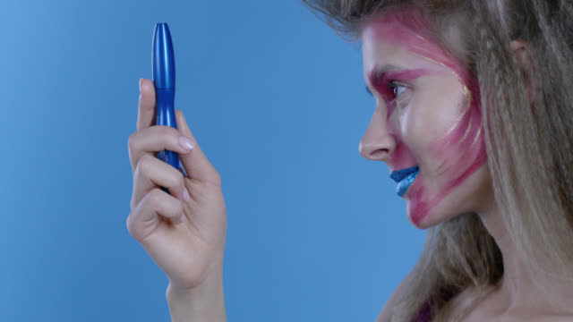 high fashion blond model in multi colored stage make-up shows blue mascara tube. fashion video. - haute couture stock videos and b-roll footage