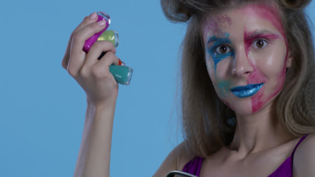 High fashion blond model in multi colored stage make-up takes out a lot of multi colored nail polish bottles from transparent plastic bag. Fashion video.