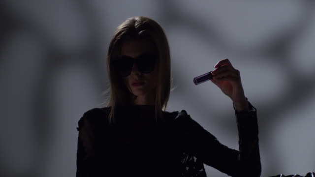 high fashion blond model in sunglasses dressed black holds lipstick in her hand. fashion video. - greasepaint stock videos and b-roll footage