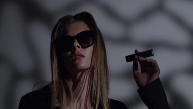 vídeos de stock, filmes e b-roll de modelo de alta moda loira com óculos escuros, vestido preto tem batom na mão dela. vídeo de moda. - maquiagem para teatro