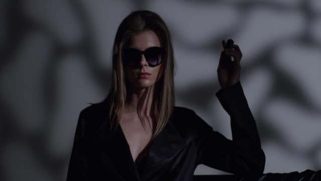 vídeos y material grabado en eventos de stock de modelo de alta moda rubia en gafas de sol vestido negro tiene lápiz labial en la mano. video de la moda. - feminidad