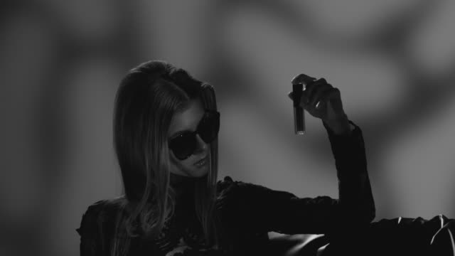 high fashion blond model in sunglasses dressed black holds lipstick in her hand. fashion video. black and white. - greasepaint stock videos and b-roll footage