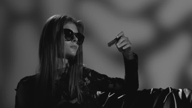 vídeos de stock, filmes e b-roll de modelo de alta moda loira com óculos escuros, vestido preto tem batom na mão dela. vídeo de moda. preto e branco. - maquiagem para teatro