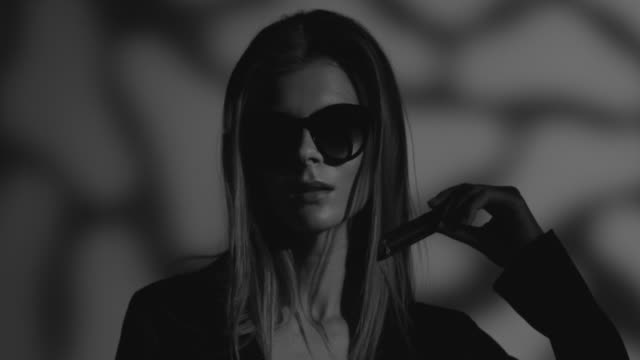 high-fashion blonde modell in schwarz gekleidet-sonnenbrille hält lippenstift in der hand. mode video. schwarz und weiß. - fashion show stock-videos und b-roll-filmmaterial