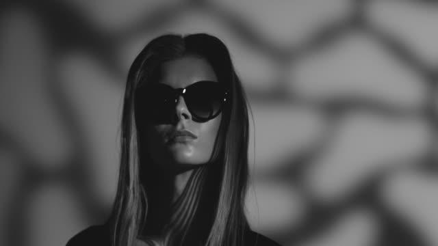 vídeos de stock, filmes e b-roll de modelo de alta moda loira com óculos escuros, vestido preto se move. vídeo de moda. preto e branco. - maquiagem para teatro