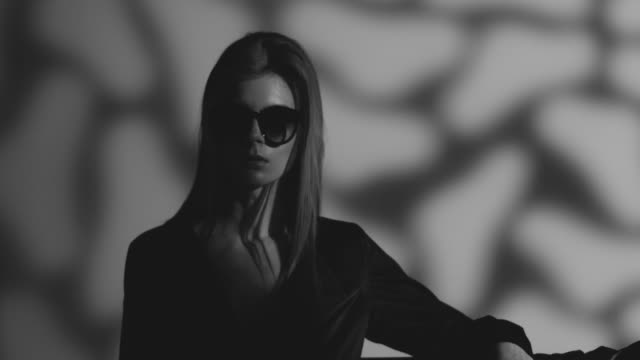 high fashion blond model in sunglasses dressed black moves. fashion video. black and white. - fascino video stock e b–roll