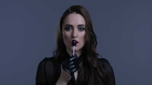 high fashion model holds lollypop in her hand, licking it. fashion video. - lollipop stock videos & royalty-free footage