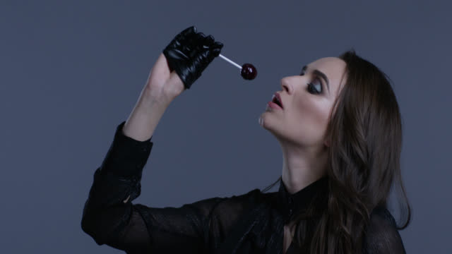 high fashion model holds lollypop in her hand, licking it. fashion video. - lollipop stock videos and b-roll footage