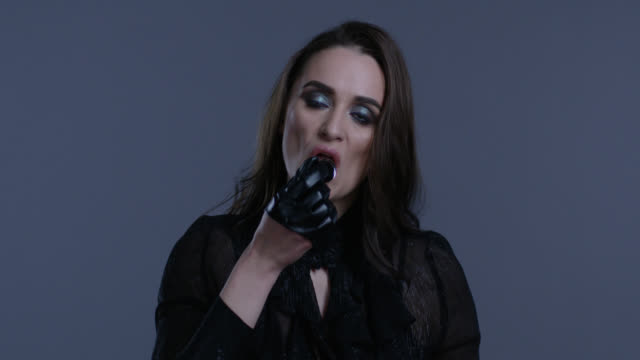 high fashion model in black leather gloves swallows black nail polish bottle. fashion video. - seductive women stock videos & royalty-free footage