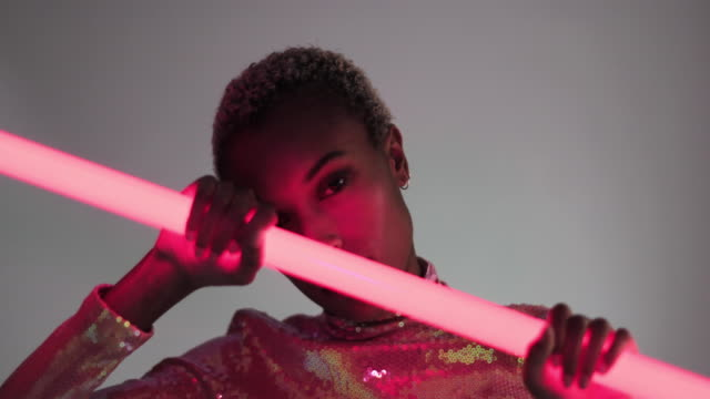 high fashion model posing with neon tubes in studio - neon lighting stock videos & royalty-free footage