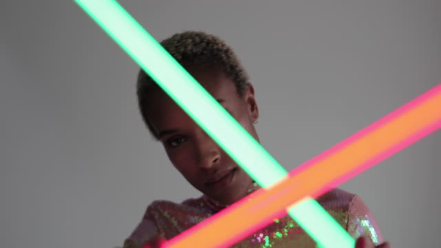 high fashion model posing with neon tubes in studio - music video stock videos & royalty-free footage