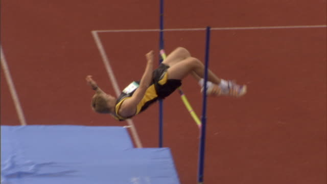 ws pan high jumper clearing bar, falling onto bag, and backflipping in victory/ sheffield, england. - バク転点の映像素材/bロール
