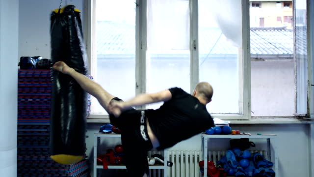 high kick on kickboxing bag - punch bag stock videos & royalty-free footage