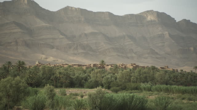a high mountain range overlooks greenery and building tops in north africa. - religious illustration stock videos and b-roll footage