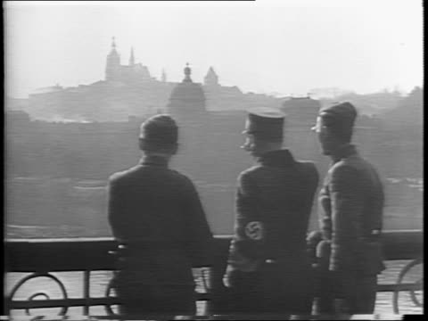 high pan of prague cityscape / three men stand in silhouette on balcony / people tear and knock down nazi signs / man with hammer knocks german... - nazi swastika stock videos & royalty-free footage