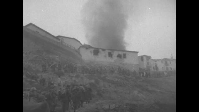 vidéos et rushes de high plains above the city of teruel / nationalist soldiers fire machine guns and field artillery into the distant town / smoke rises from burning... - évasion