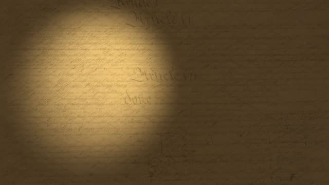 high resolution 4k video of a beam of light moving on the us constitution pages. - law stock videos & royalty-free footage